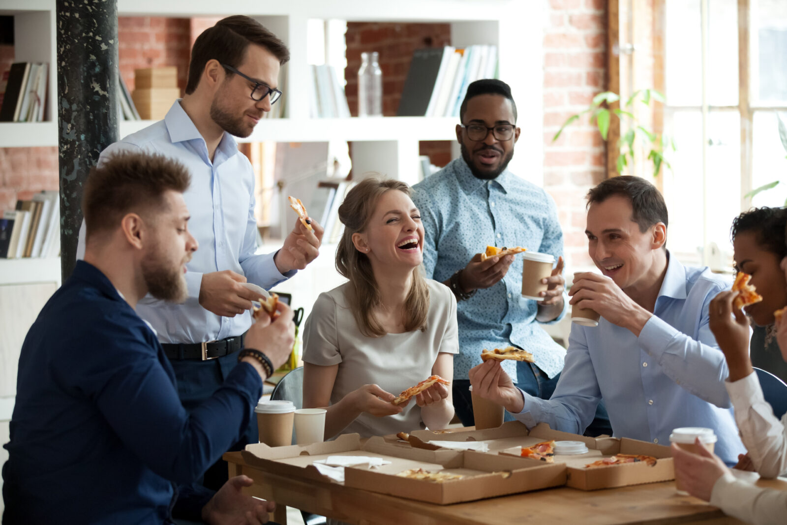 Happy diverse team people talking laughing at funny joke eating ordered pizza in office